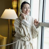 Taiwanese mid adult woman in bathrobe talking on phone and looking out window.