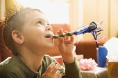 Caucasian boy at  birthday party  blowing noisemaker.
