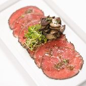 Pepper charred beef carpaccio with mushrooms.