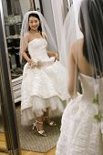 Asian bride admiring shoes in mirror.
