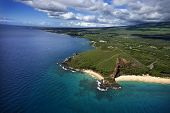 Aerial of Maui, Hawaii coastline with crater and cliffs and beach on Pacific ocean.