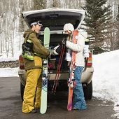 Young couple wearing winter clothes unloading ski equipment from vehicle smiling and laughing.