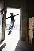 Woman running and jumping through open door from building to sunny outside.