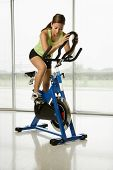 Mid adult Asian woman pedaling exercise bicycle indoors.