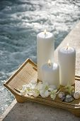Lit pillar candles on tray with white orchids beside pool.