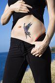 Caucasian woman exposing tattoo of fairy on stomach.