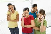 Preteen girls of mutiple ethnicities talking on cell phones.
