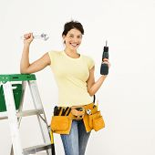 Woman standing in home with ladder and holding tools smiling.