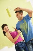 Attractive couple standing in front of partially painted wall playfully putting paint on each other.