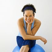 Portrait of young woman sitting on fitness balance ball smiling.