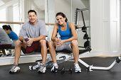 Man en vrouw zittend op oefening machine pratende bedrijf waterflessen.