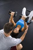 Man assisting woman lifting weights at gym.