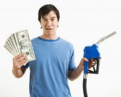 Asian young man with confused expression holding money and gas pump nozzle.