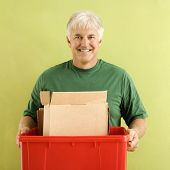 Portrait of smiling adult man holding recycling bin full of cardboard.