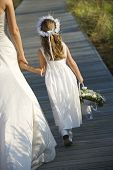 Cropped rear view of a bride walking and holding hands with a flower girl on the boardwalk. Vertical