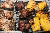stock photo of barbie  - a barbecue rack on the grill with chicken portions lamb chops and sweetcorn - JPG