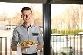 Handsome waiter with plate of salad at restaurant poster