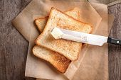 Tasty toasted bread and butter on wooden table poster