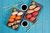 Delicious Set Of Nigiri Sushi Served With Traditional Soy Sauce And Chopsticks, Flat Lay On Blue Pla poster