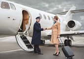 Full Length Outgoing Businesswoman Welcoming With Glad Pilot At Airfield. Career Concept poster