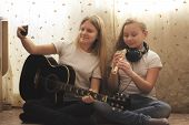 Two Female Teens Playing Musical Instruments And Making Selfie Sitting On The Floor At Home, Youth H poster