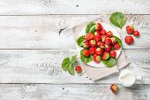 Heap Of Fresh Strawberries In A Bowl With Leaves And Cream On White Wooden Background. Top View Poin poster