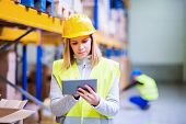 Young Woman Worker Or Supervisor With Tablet. Warehouse Workers Controlling Stock. poster