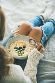 Healthy Winter Breakfast In Bed. Woman In White Woolen Sweater And Shabby Jeans Eating Vegan Almond  poster