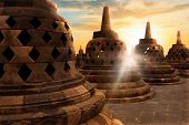 Many Huge Stone Buddhist Stupas Against The Background Of The Sunrise With Rays Of Light In The Boro poster