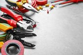 Different electrical tools on grey background poster
