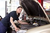 Portrait of a happy mechanic woman working on a car in an auto repair shop