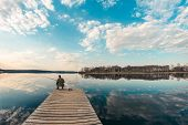 Alone Fisherman Sitting On The Pier Far Out Into The Lake, The Weather Is Calm poster