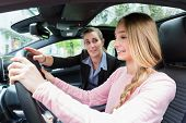 Student on wheel of car in driving lesson with her teacher learning to drive poster