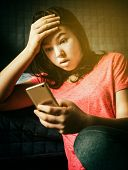 Bad news. Sad teenager girl looks at smartphone screen Bad news.  poster