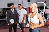 happy female gym trainer portrait with colleagues in background