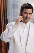 Hispanic man in tuxedo talking on cell phone