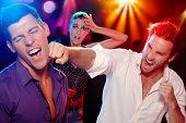 Dos jóvenes cantándola en el club nocturno para una mujer, que está preocupada en el fondo.