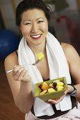Asian woman eating fruit