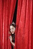 image of beauty pageant  - Hispanic beauty queen peeking through curtains - JPG