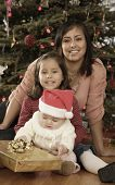Hispanic mother and children in front of Christmas tree