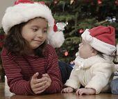 Hispanic girl smiling at baby sibling on Christmas