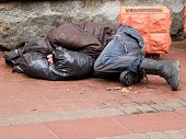 Homeless man sleeps on a pavement