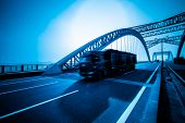 truck speeding through a bridge of ciy,blue toned.