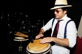 stock photo of bongo  - Portrait of young male percussionist playing cuban drums against black background - JPG