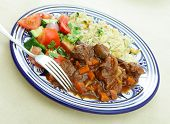 A beef tagine stew meal served with rice cooked with nuts and spices and a tossed salad of tomato, cucumber and coriander