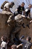 POCONO, PA - APR 29: A participant gets help to get up and over the Berlin Walls obstacle at Tough M