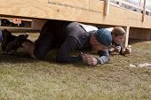 POCONO MANOR, PA - APR 28: Entrants crawl under an obstacle at Tough Mudder on April 28, 2012 in Pocono Manor, PA. The course is designed by British Special Forces.