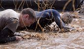 POCONO MANOR, PA - APR 28: Two men crawl through water under electrified wires at Tough Mudder event