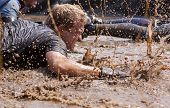 POCONO MANOR, PA - APR 28: A man crawls through water under electrified wires at Tough Mudder event