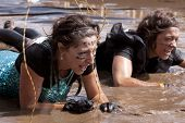 POCONO MANOR, PA - APR 28: Two women crawl through water under electrified wires at Tough Mudder eve